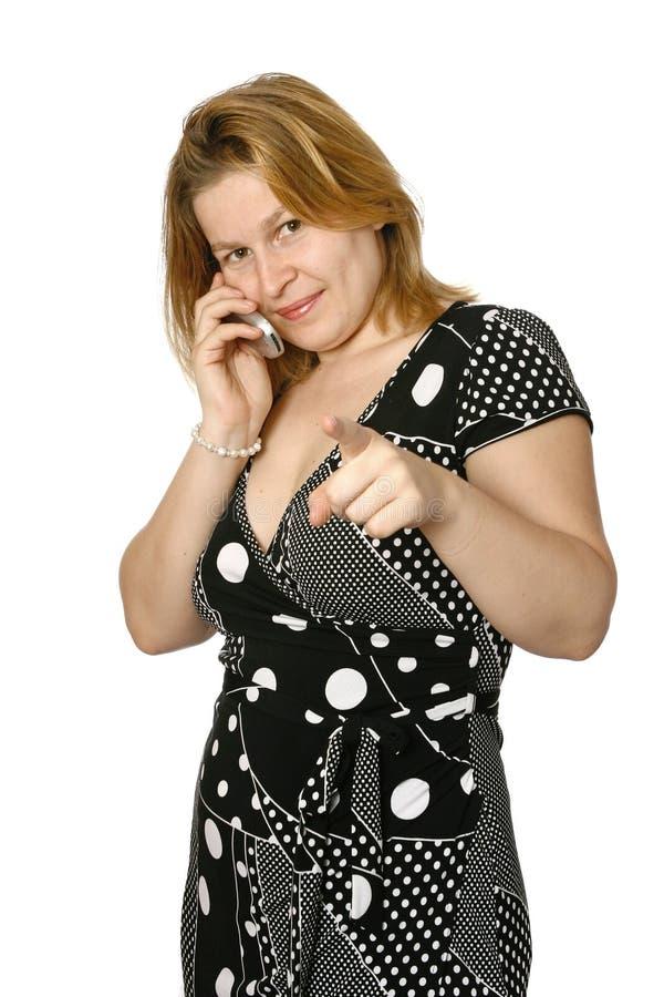 Mulher no telemóvel com dedo que aponta no visor imagem de stock