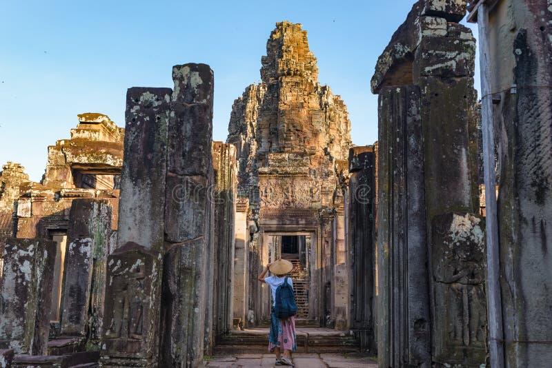 Mulher no templo de Bayon que olha as caras de pedra, Angkor Thom, céu azul claro da luz da manhã Conceito da meditação do budism fotografia de stock