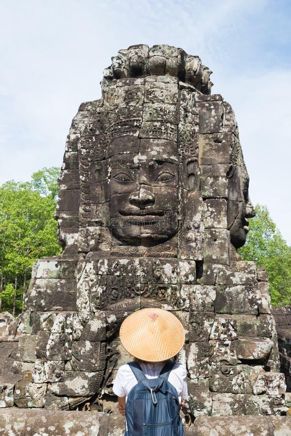 Mulher no templo de Bayon que olha as caras de pedra, Angkor Thom, c?u azul claro da luz da manh? Conceito da medita??o do budism imagem de stock