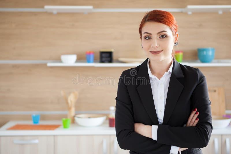 Mulher no terno de negócio que levanta em sua cozinha fotografia de stock royalty free