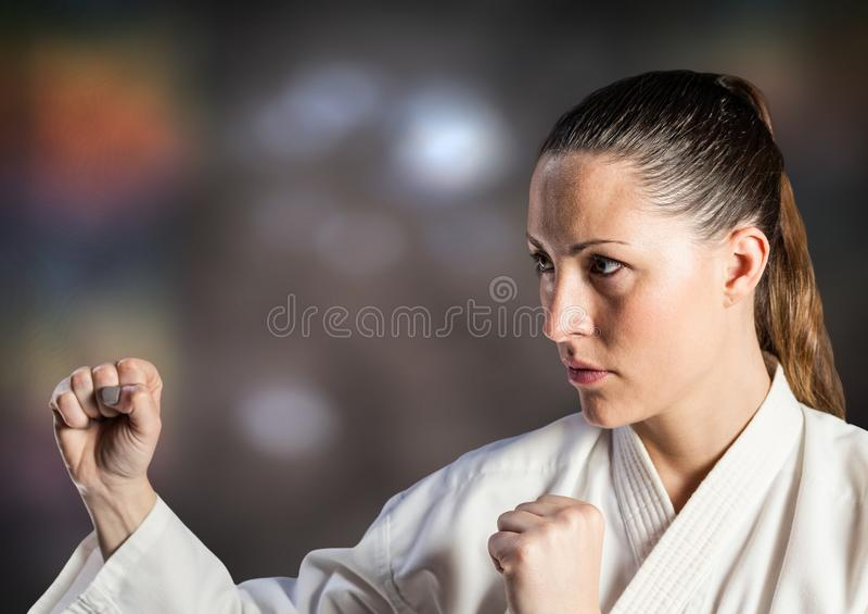 Mulher no terno do karaté que levanta contra o fundo marrom obscuro fotos de stock