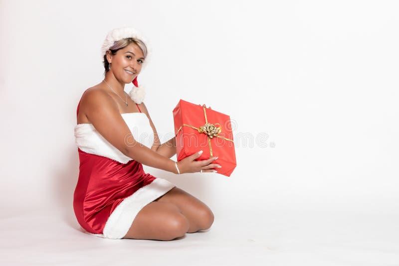 A mulher no traje de Santa está guardando um presente do Natal fotografia de stock