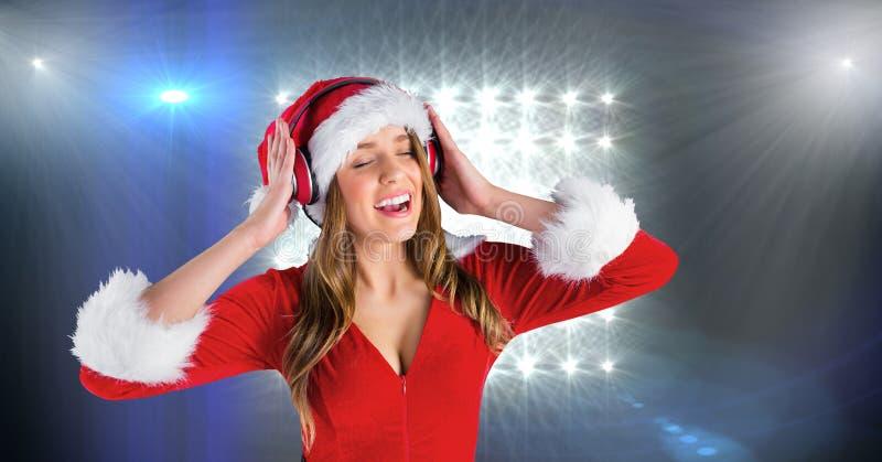 Mulher no traje de Santa que escuta a música em fones de ouvido fotografia de stock royalty free