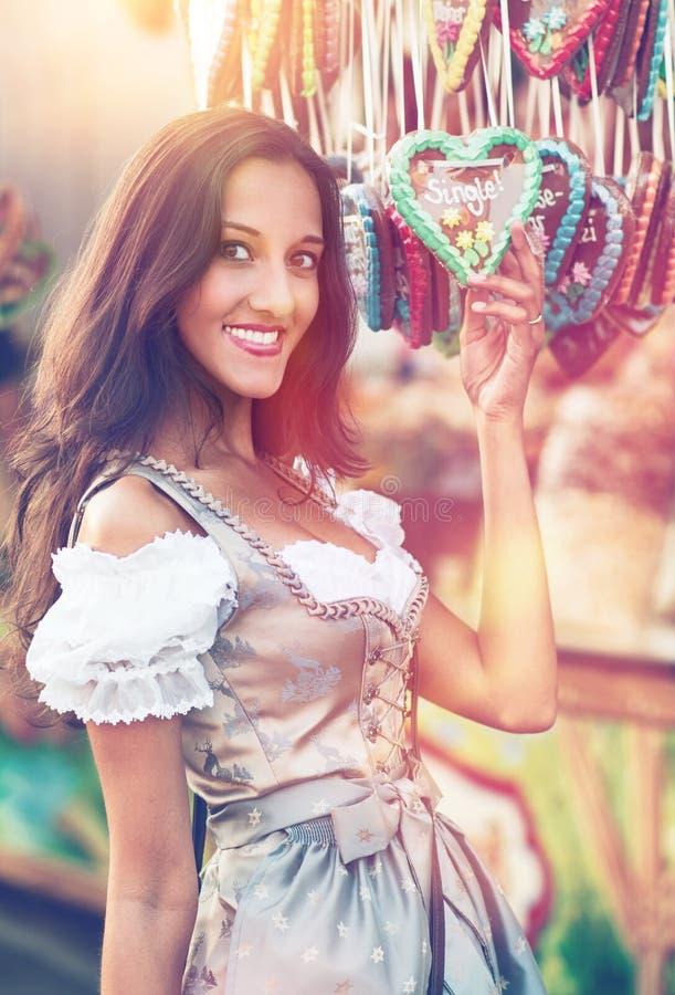 Mulher no traje do Dirndl com coração do pão-de-espécie foto de stock royalty free