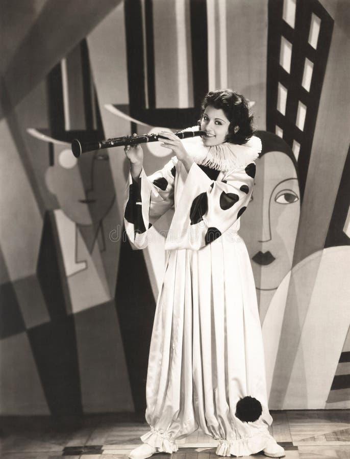Mulher no traje do palhaço que joga o clarinete fotografia de stock