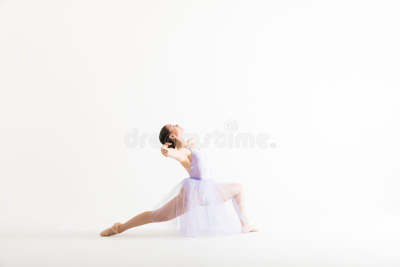 Mulher no tutu que executa uma rotina da dança sobre o fundo branco fotografia de stock royalty free