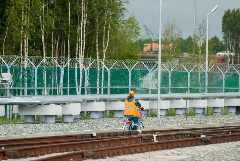 A mulher no uniforme de trabalho vai pela bicicleta imagens de stock