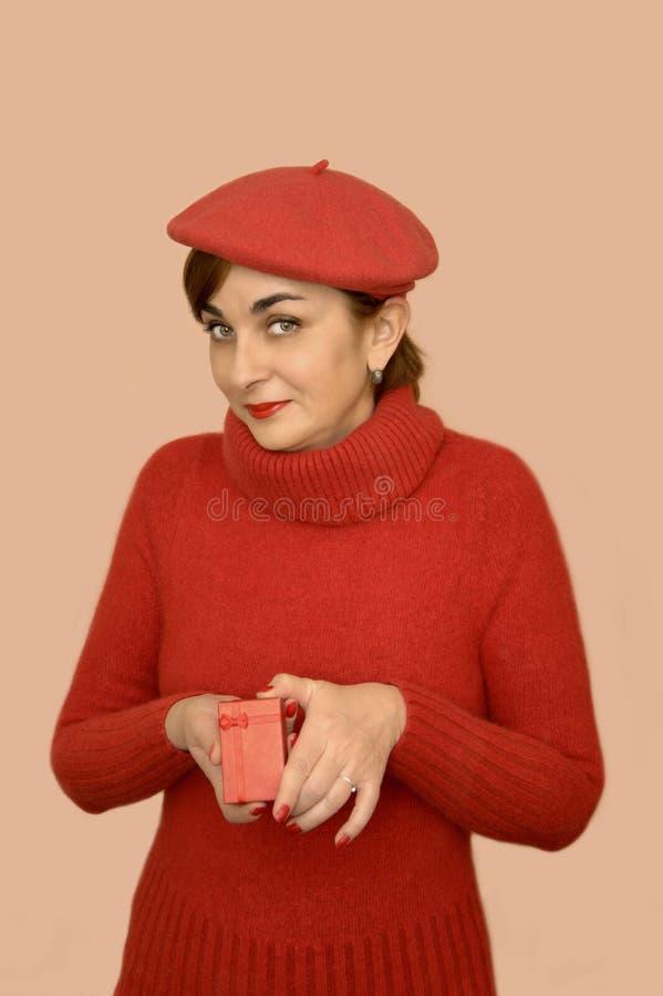 Mulher no vermelho com a boina que guarda um presente fotos de stock royalty free