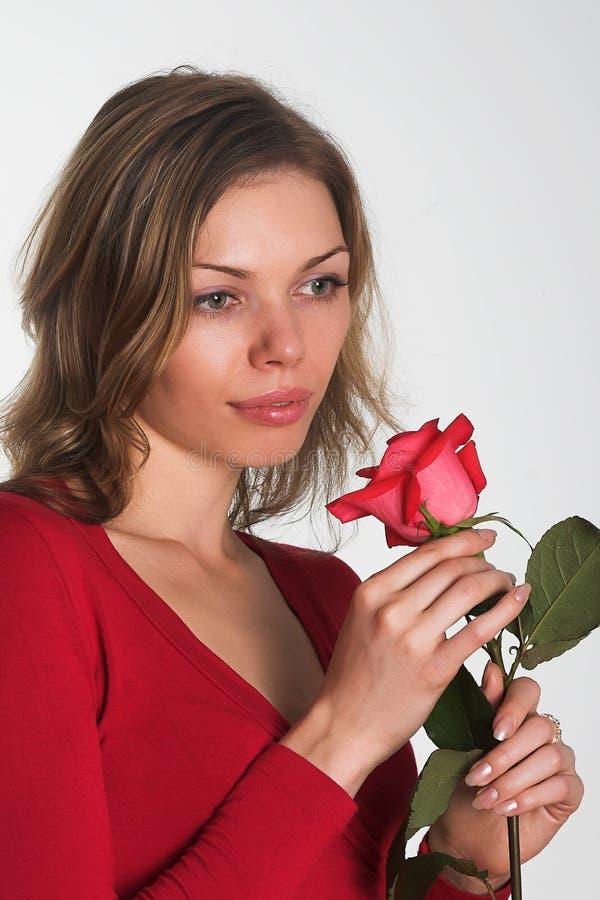 A mulher no vermelho com uma flor imagem de stock