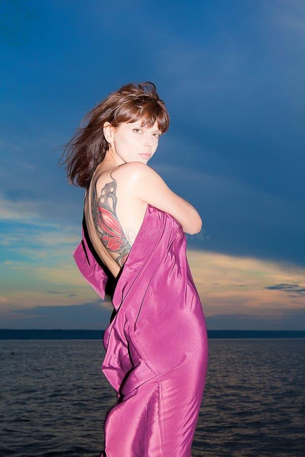 Mulher no vestido aberto com tatuagem da borboleta nela para trás fotografia de stock royalty free
