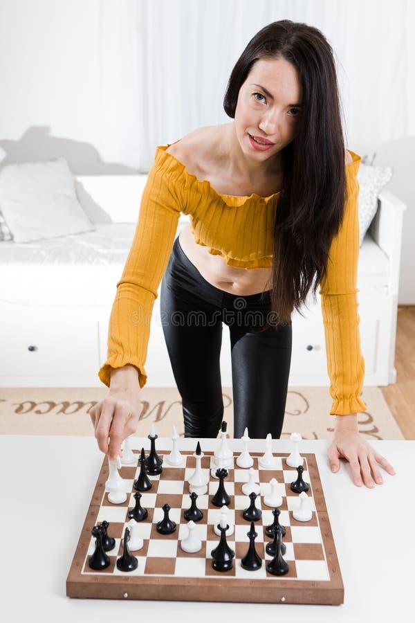 Mulher no vestido amarelo que senta-se na frente da xadrez - movimento do cavalo branco foto de stock