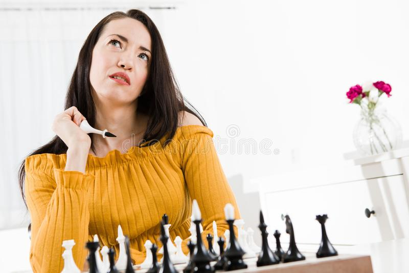 Mulher no vestido amarelo que senta-se na frente da xadrez - movimento o rei fotografia de stock
