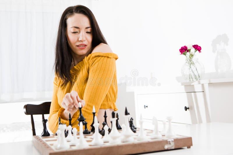 Mulher no vestido amarelo que senta-se na frente da xadrez - movimento da rainha fotografia de stock