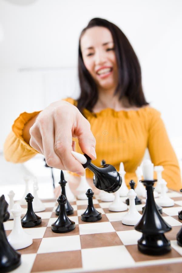 Mulher no vestido amarelo que senta-se na frente da xadrez - posta no checkmate imagens de stock royalty free