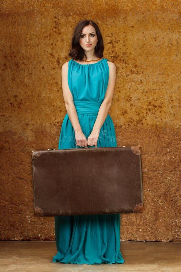 Mulher no vestido azul com mala de viagem imagens de stock royalty free