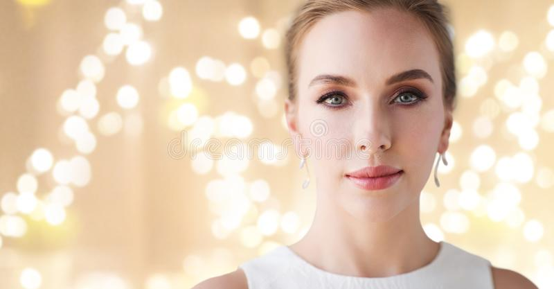 Mulher no vestido branco com brinco do diamante foto de stock royalty free