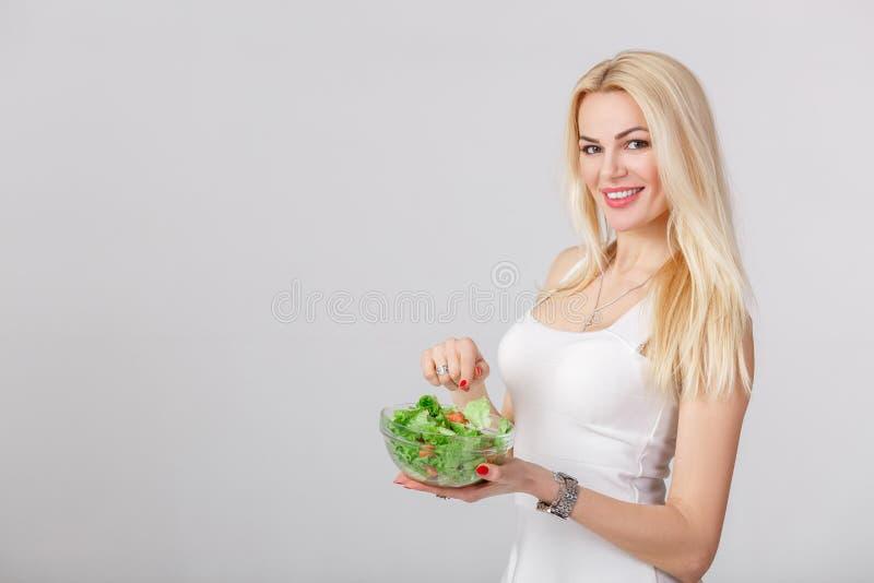 Mulher no vestido branco com salada fresca fotografia de stock royalty free