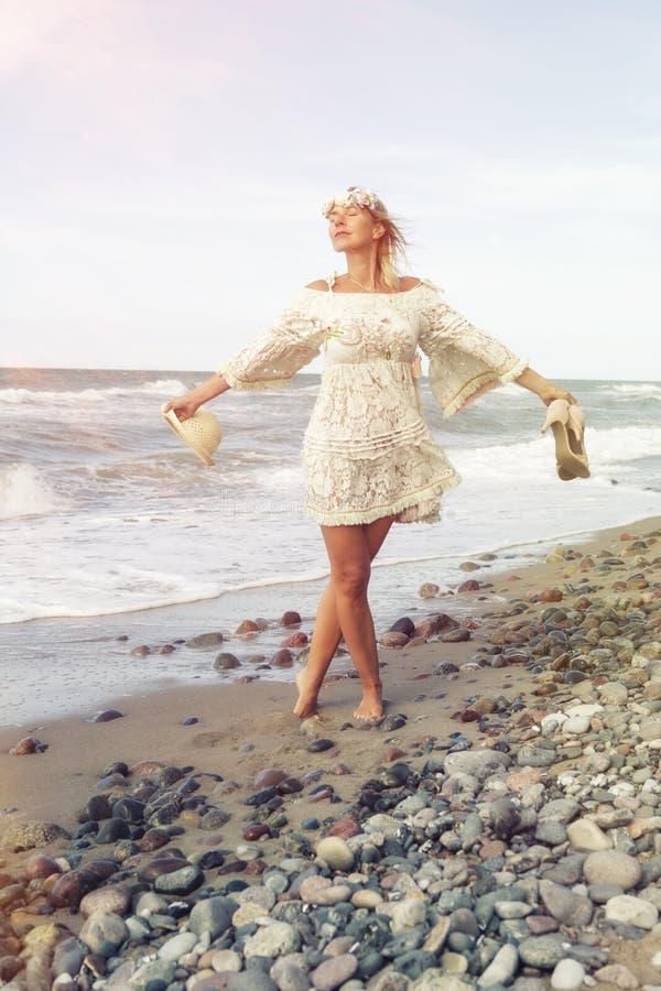 Mulher no vestido branco que anda com os pés descalços na praia imagem de stock