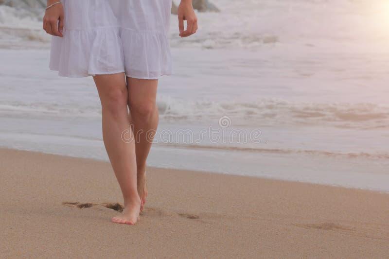 Mulher no vestido branco que anda na praia da areia imagem de stock