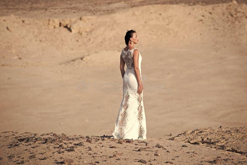 Mulher no vestido branco que está em dunas de areia no deserto fotografia de stock royalty free