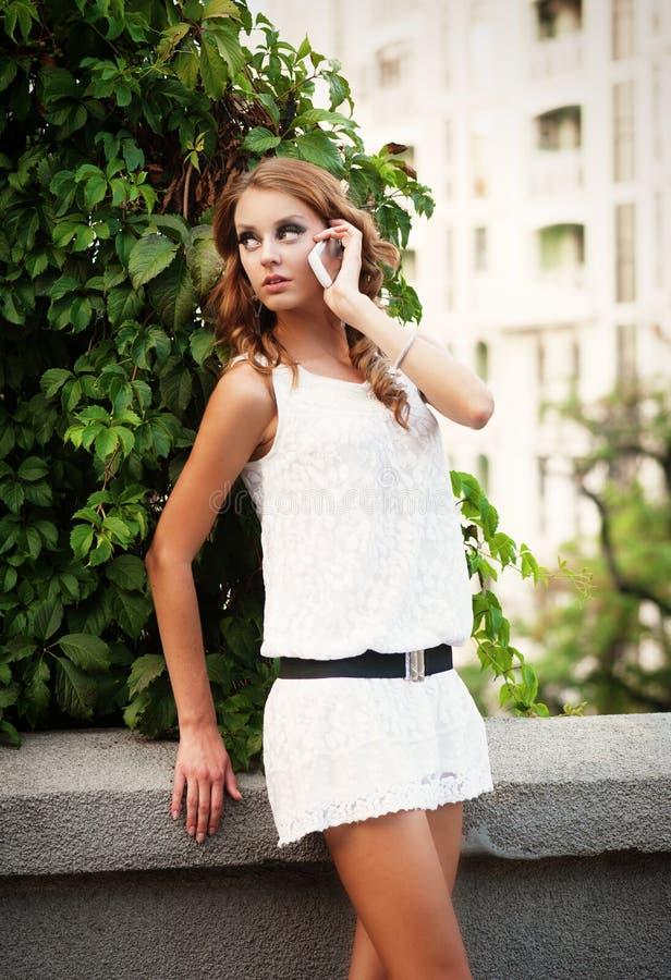 Mulher no vestido branco que fala no telefone móvel imagens de stock royalty free