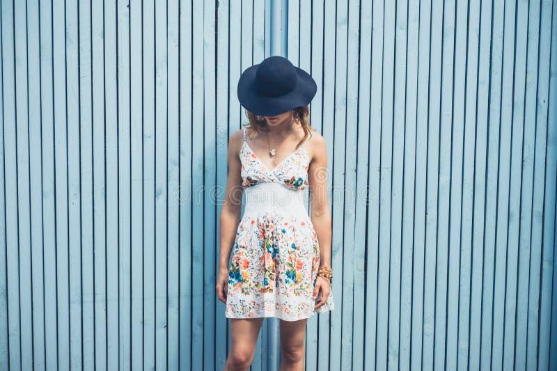 Mulher no vestido com chapéu fora pela cerca azul imagem de stock