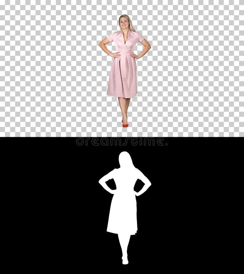 Mulher no vestido com mãos nos quadris que anda ao olhar a câmera, Alpha Channel foto de stock
