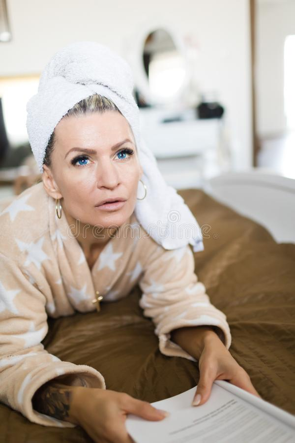 Mulher no vestido de molho que tem a toalha na cabeça e no livro de leitura imagem de stock royalty free