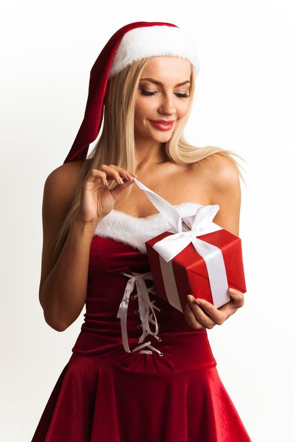 A mulher no vestido de Santa desembala o presente foto de stock royalty free