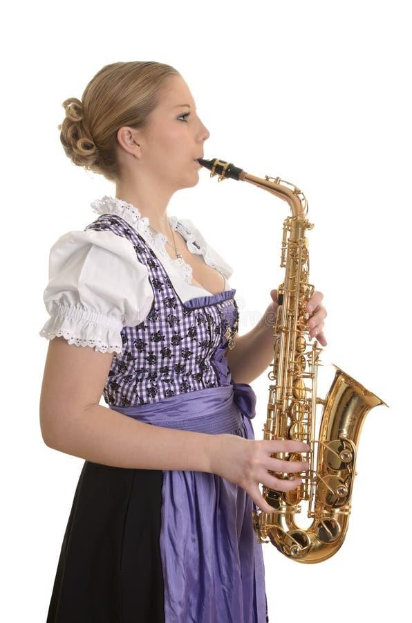 Mulher no vestido do dirndl que joga o saxofone fotos de stock royalty free