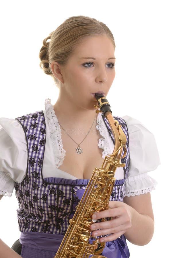 Mulher no vestido do dirndl que joga o saxofone imagens de stock