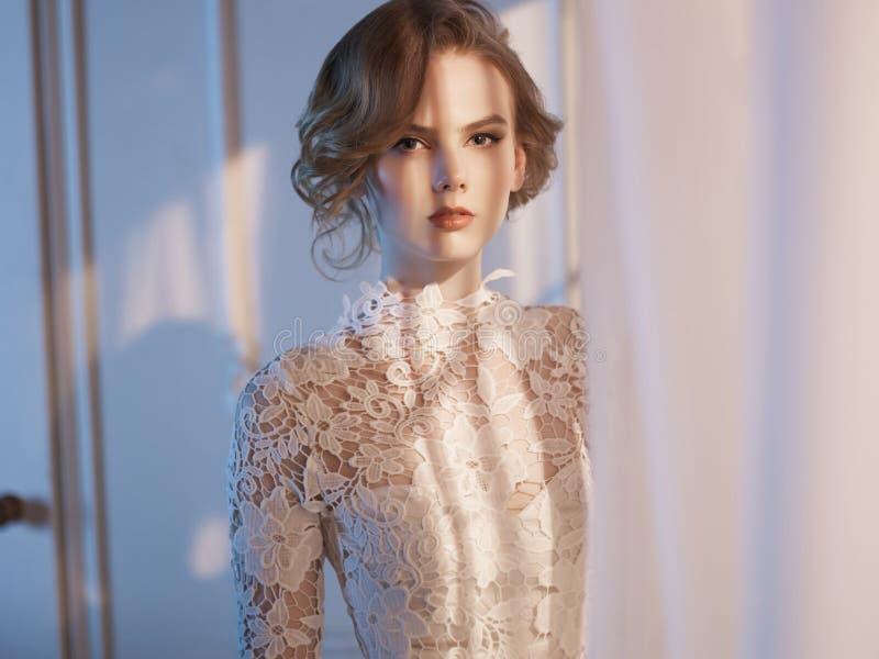 Mulher no vestido do laço na janela fotografia de stock royalty free