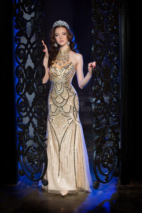 A mulher no vestido do lux com coroa gosta da rainha, princesa, partido das luzes fotografia de stock royalty free