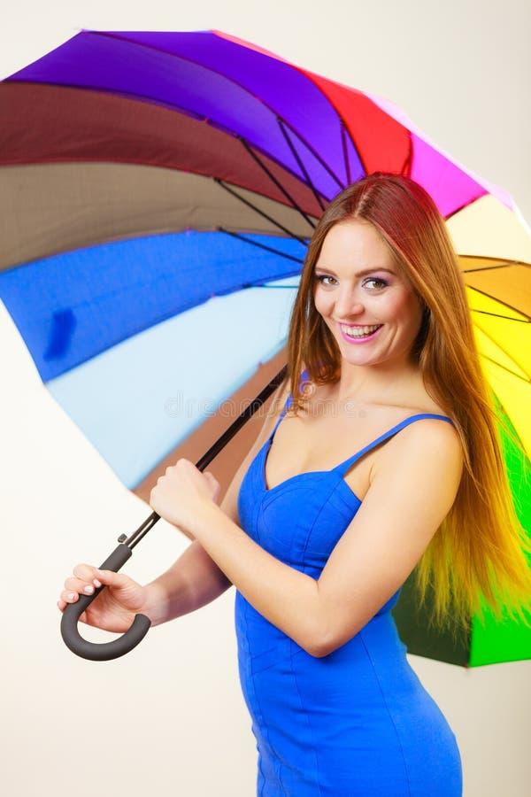 A mulher no vestido do ver?o guarda o guarda-chuva colorido fotografia de stock royalty free