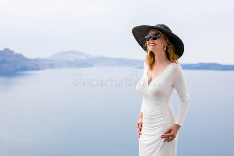Mulher no vestido e no chapéu negro brancos foto de stock