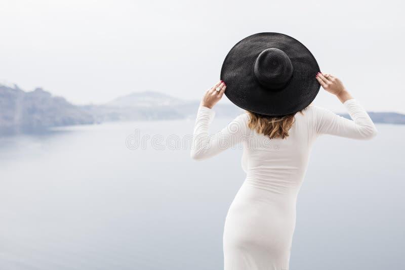 Mulher no vestido e no chapéu negro brancos de atrás imagem de stock