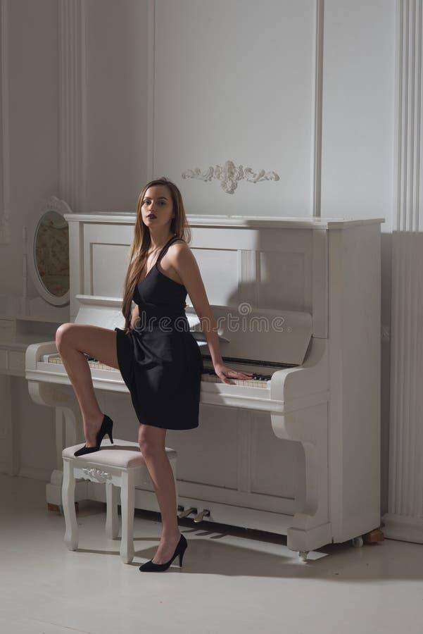 Mulher no vestido elegante do coctail perto do piano, conceito da elegância Pianista sensual no instrumento musical Elegância e e imagem de stock royalty free