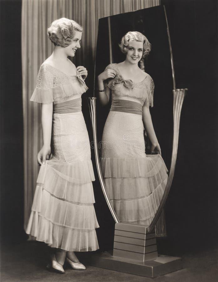 Mulher no vestido estratificado que olha sua reflexão no espelho foto de stock royalty free