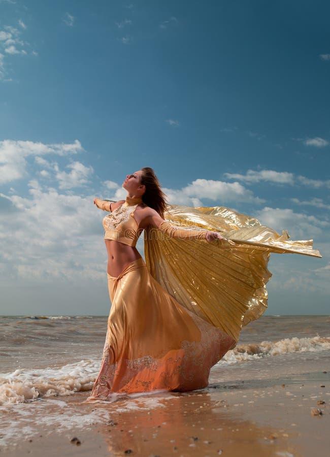 Mulher no vestido exótico que está na praia fotos de stock