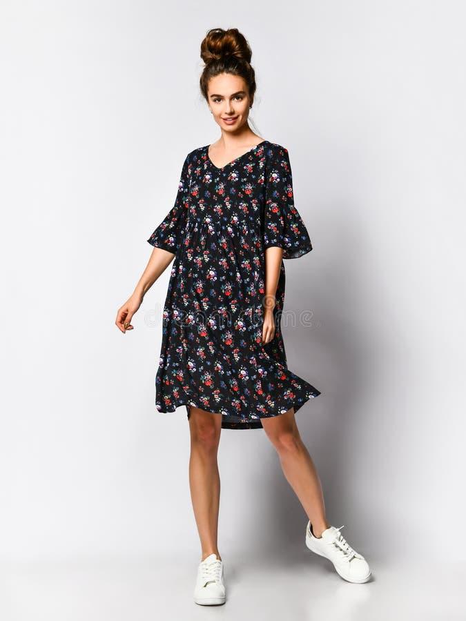 Mulher no vestido floral longo na loja da forma - retrato da menina em uma loja de roupa em um vestido maxi do ver?o foto de stock royalty free