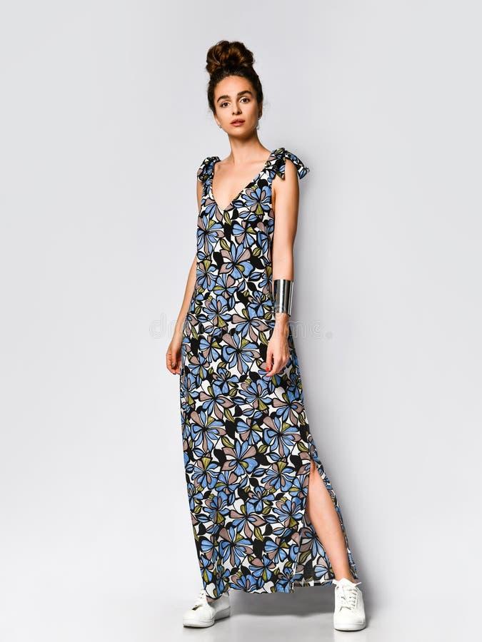 Mulher no vestido floral longo na loja da forma - retrato da menina em uma loja de roupa em um vestido maxi do ver?o imagens de stock