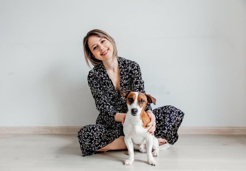Mulher no vestido na moda que senta-se no assoalho com cão imagens de stock