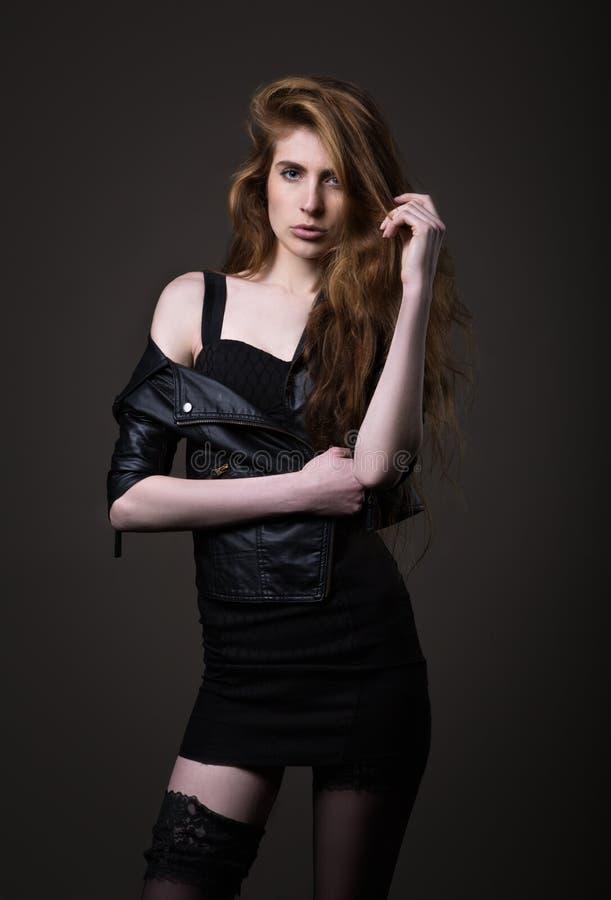 Mulher no vestido, no casaco de cabedal e em meias pretos imagens de stock royalty free