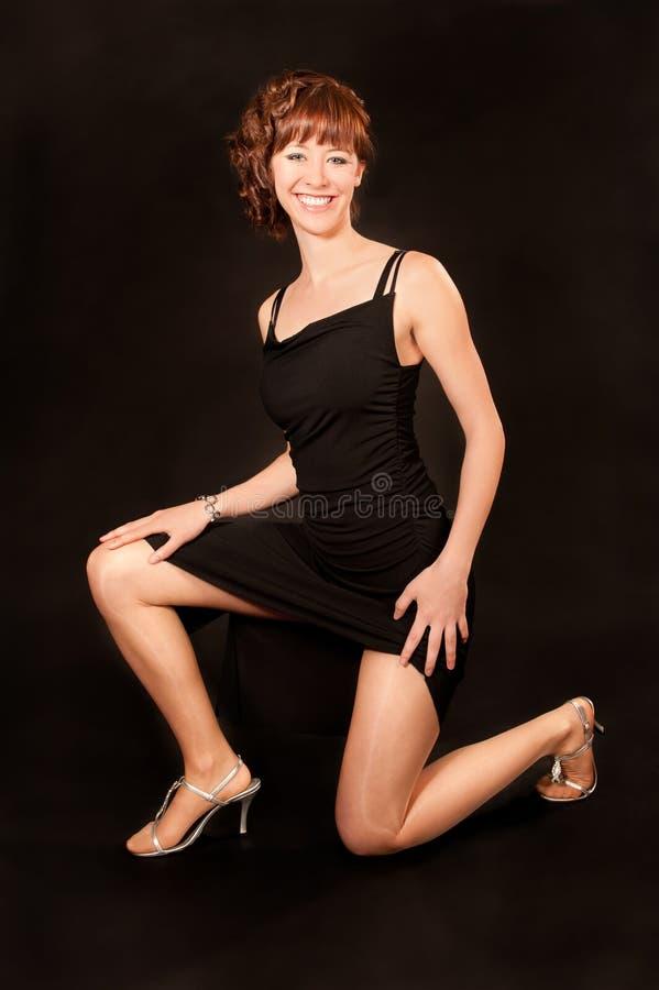 Mulher no vestido preto e nos saltos elevados fotografia de stock