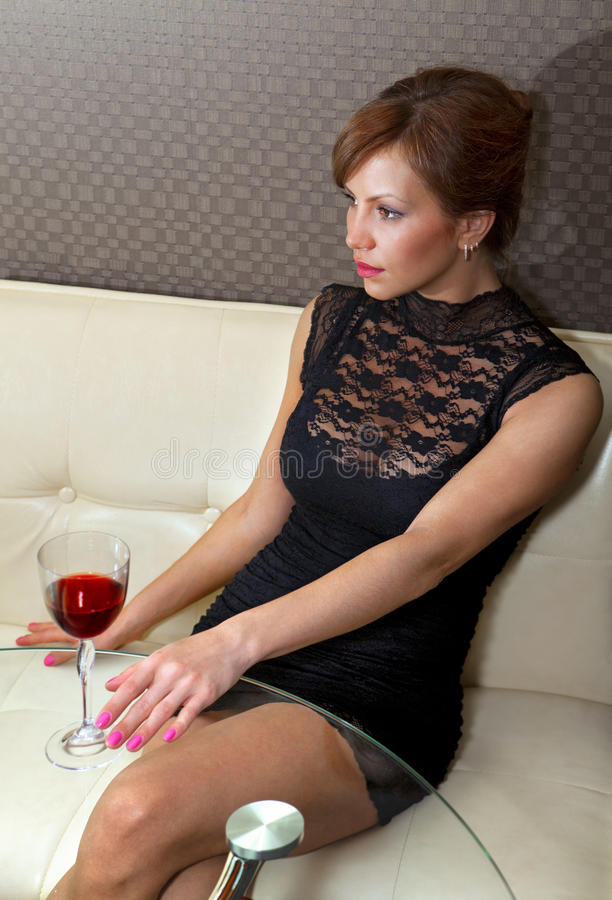 Mulher no vestido preto no ll do sofá fotografia de stock
