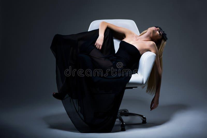 Harmonia & sensualidade. Fêmea loura romântica no vestido preto que descansa na poltrona. Satisfação fotografia de stock royalty free