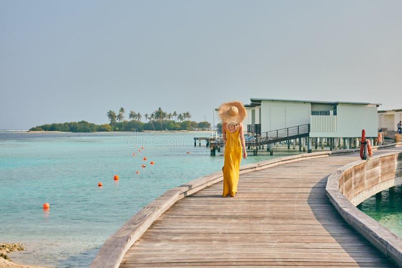 Mulher no vestido que anda no passeio ? beira mar tropical da praia imagem de stock royalty free