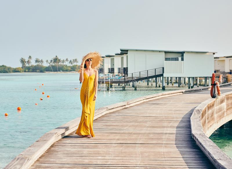 Mulher no vestido que anda no passeio ? beira mar tropical da praia imagens de stock royalty free