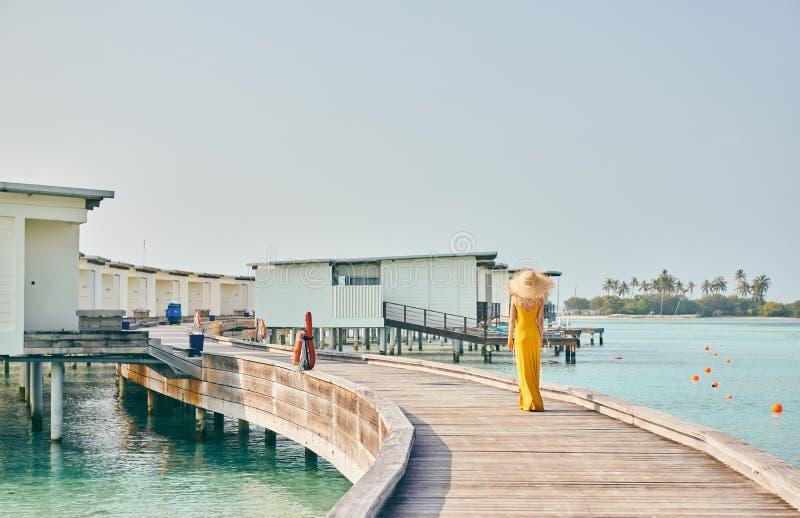 Mulher no vestido que anda no passeio ? beira mar tropical da praia imagens de stock