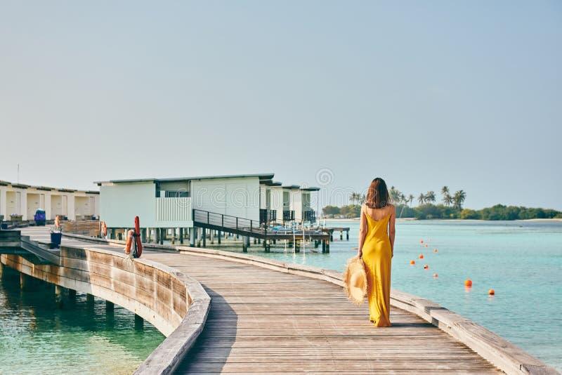 Mulher no vestido que anda no passeio ? beira mar tropical da praia fotografia de stock royalty free